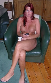 Redhead mature beauty posing naked on chair