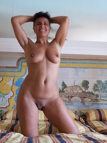 Older woman posing naked on the bed and showing her great body: puffy pussy lips, round..